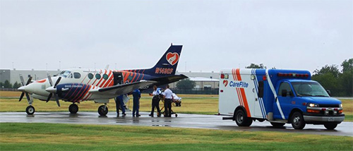 A FLIGHT NURSE HELPS WITH A PATIENT TRANSFER FROM AN AMBULANCE TO A PLANE