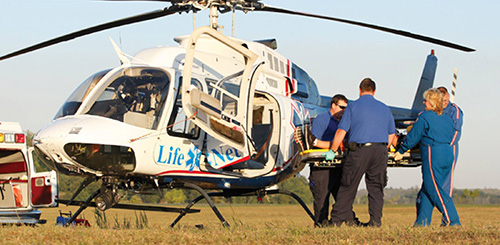 A MEDICAL TEAM LOADS THE VICTIM OF AN ACCIDENT ONTO A LIFE FLIGHT HELICOPTER