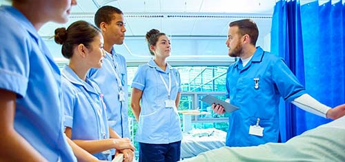 A NURSING INSTRUCTOR HELPS STUDENTS WITH THEIR CLINICAL ROTATIONS