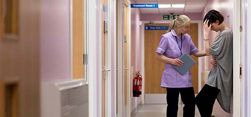 A PSYCHIATRIC NURSE CHECKS ON ONE OF HER PATIENTS