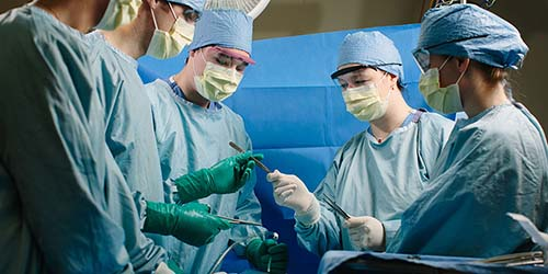 A SURGICAL TECH HANDS AN INSTRUMENT TO THE RESIDENT SURGEON