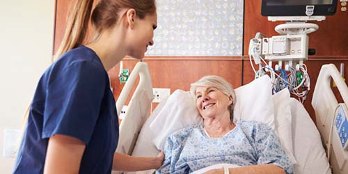 AN ONCOLOGY NURSE HELPS A PATIENT WITH HER MEDICATION