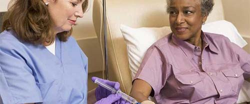 AN ONCOLOGY NURSE TALKS TO HER PATIENT WHILE GIVING AN INFUSION