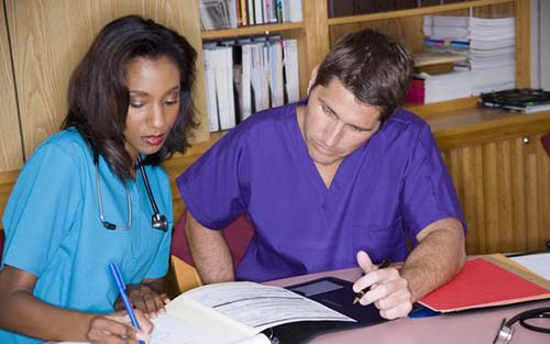 TWO PSYCHIATRIC NURSES GO OVER PATIENT CHARTS TOGETHER