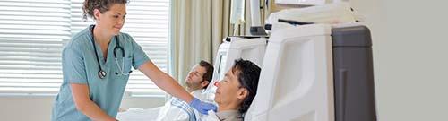A DIALYSIS NURSE CHECKS A PATIENTS FISTULA