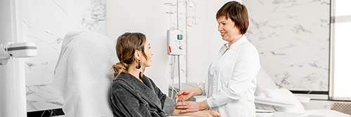 A DIALYSIS NURSE WORKS WITH HER PATIENT