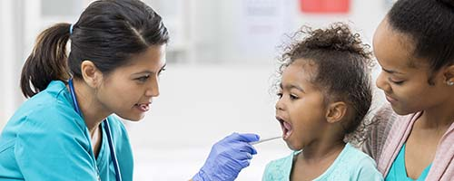 A PEDIATRIC NURSE TAKES A SWAB FROM HER PATIENT FOR TESTING