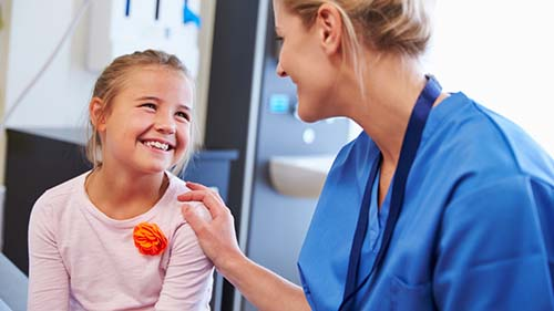 A PEDIATRIC ONCOLOGY NURSE LAUGHS WITH ONE OF HER PATIENTS