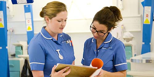 2 REGISTERED NURSES DISCUSS THE CARE OF A PATIENT